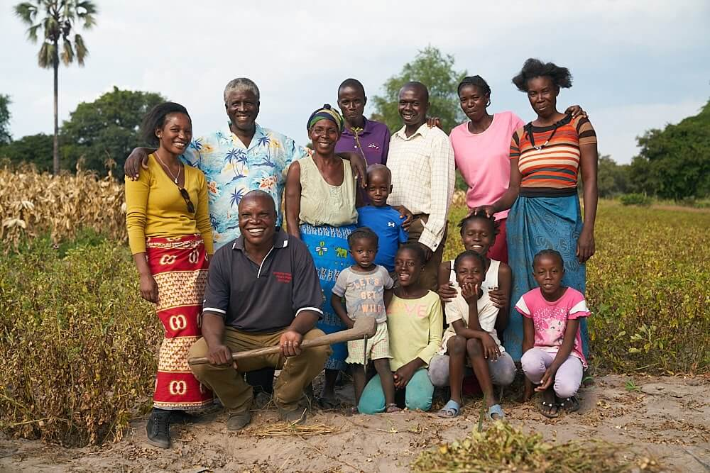 Group portrait of a smiling group of farmers and their children