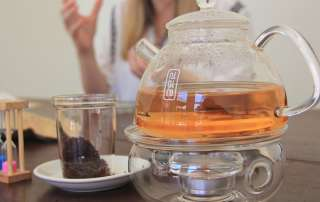 Honeybush tea brews in a glass teapot over a candle.