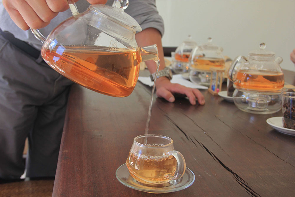 Two people sit opposite each other at a table lined with teapots, smiling and sipping on honeybush tea.