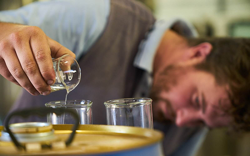 A man pours liquid from one beeker into another.