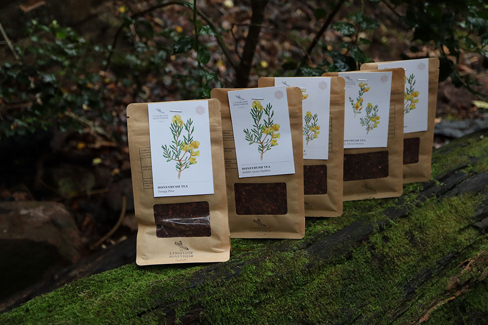 Langkloof Honeybush Co.'s signature blends in packages lined up on a mossy piece of wood.
