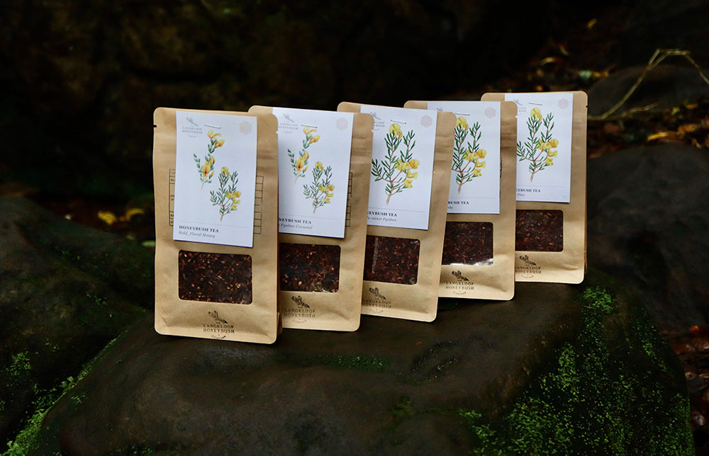 The Langkloof Honeybush Company tea packages on display in a row.
