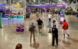 The large expo hall with people walking around and many stands on display.